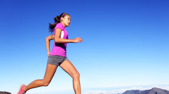 Running sports fitness runner woman jogging. Female athlete training outdoor under blue sky in amazing nature. Multiracial Asian Caucasian female fitness model exercising healthy lifestyle outside.